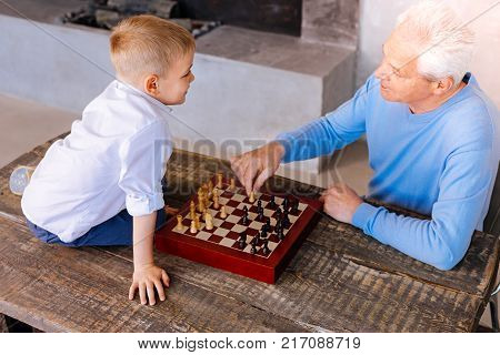 Time together. Positive smart senior man sitting opposite his grandson and holding a chess piece while teaching him to play chess