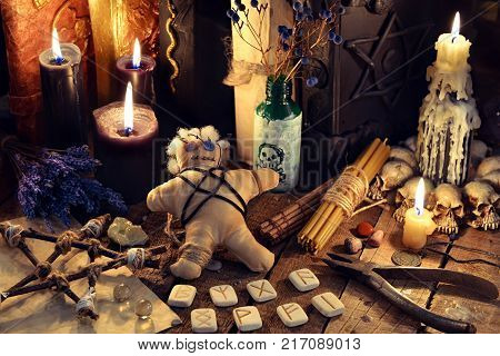 Voodoo doll, black candles, pentagram and old book on witch table. Occult, esoteric, divination and wicca concept. Mystic, voodoo and vintage background