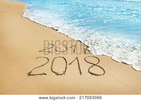 digits 2017 and 2018 on the sand seashore - concept of New Year and Xmas and passing of time