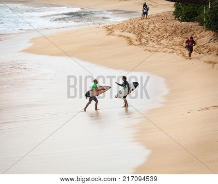 SUNSET BEACH HAWAII USA - DECEMBER 2, 2017: Competitive surfers walking and talking on beach at the 2017 Vans World Cup of Surfing competition at Sunset Beach on Oahu's scenic North Shore. This is the second of three surfing competitions and Conner Coffin