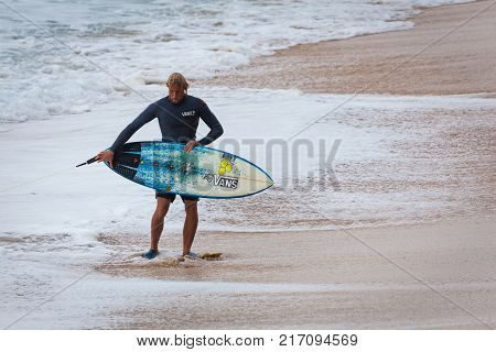 SUNSET BEACH HAWAII USA - DECEMBER 2, 2017: Competitive surfer with surfboard walking on beach at the 2017 Vans World Cup of Surfing competition at Sunset Beach on Oahu's scenic North Shore. This is the second of three surfing competitions and Conner Coff