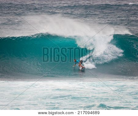 SUNSET BEACH HAWAII USA - DECEMBER 2: Competitive surfers walking on beach at the 2017 Vans World Cup of Surfing competition at Sunset Beach on Oahu's scenic North Shore. This is the second of three surfing competitions and Conner Coffin took first place.