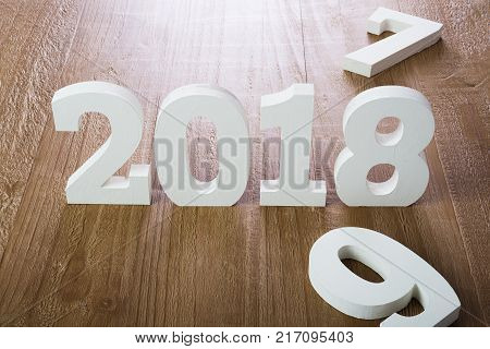 White digits 2018 and digit 7 and 9 on rustic wooden background as concept of New Year and Christmas.