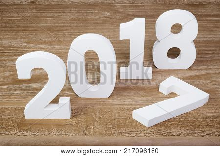 White digits 2018 and digit 7 on rustic wooden background as concept of New Year and Christmas.