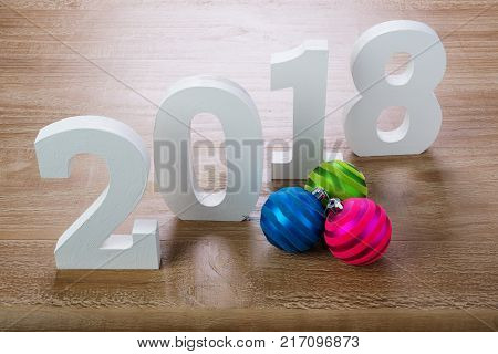 White digits 2018 with Christmas balls on rustic wooden background as concept of New Year and Christmas.