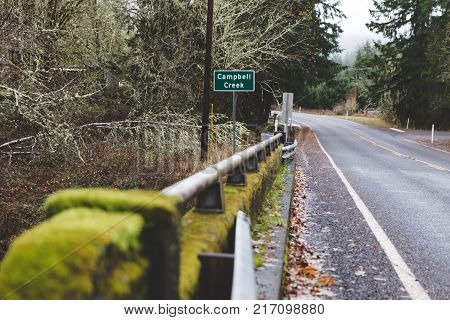 Mossy metal guard rail and sign with