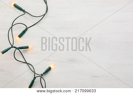 Christmas garland lights on old wooden shabby background.