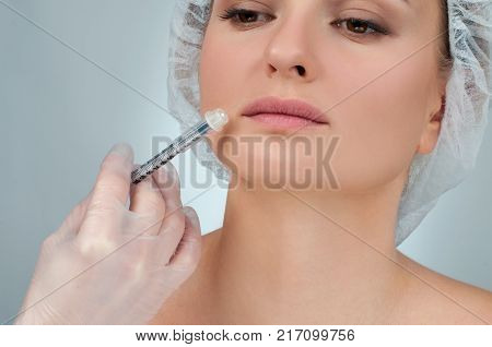 Woman is getting injection in lips. Cosmetic Treatment. Plastic Surgery. Beautiful girl receiving filler injection in lips