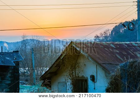 Old stucco house with rusted tin roof with sun setting behind mountains bouncing off the atmosphere and smoke from chimney in background