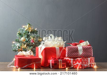 Merry Christmas & Happy new year and winter season concept.object on table and copy space background.beautiful many red gift boxes and Christmass tree with lighting on modern wood at home office desk.