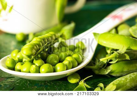 green peeled on a green background. green peas in the pods. fresh green peas. peeled peas