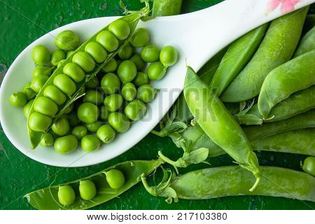 green peeled peas in a spoon on a green background. green peas in the pods. fresh green peas. peeled peas