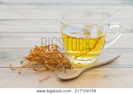 Dried Cordyceps Militaris Mushroom with Cup on wooden table background