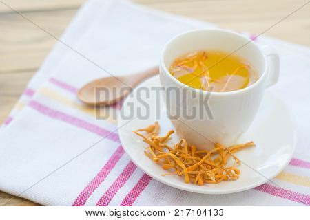 Dried Cordyceps Militaris Mushroom with Cup on white cotton fabric background
