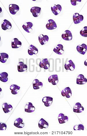 Purple rhinestone background. Heart shape texture as backdrop isolated white studio photo. Bling rhinestone crystal pattern. Rhinestones crystals as background.