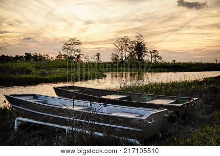 Silhouettes of tin boats sit on the shore of the Everglades in South Floridae