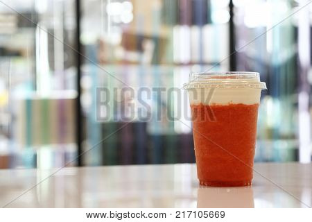 A plastic glass of strawberry smoothie with layer of cream cheese foam on blurred background and copy space, Traditional Taiwanese drink.