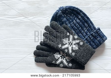 Womens winter warm accessories on white background with copy space. Woolen Knitted hat and gloves. Fashion concept. View from above top view. Flat lay.