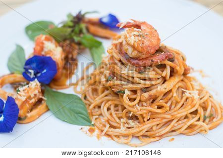 Seafood spaghetti with shrimp and squid on white plate