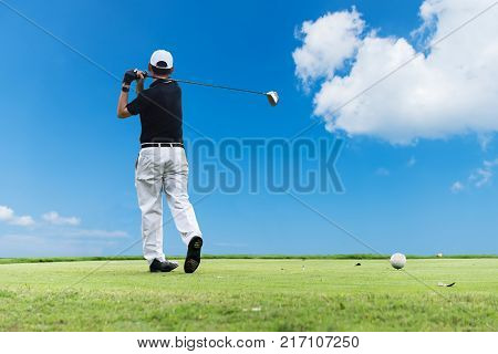 Golf player teeing offMan Swinging Golf Club with Blue Sky Background