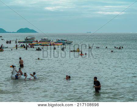 CHONBURI THAILAND - November 11 2017 View of tourists walking and playing on the beach at Nang Rum Beach (Sattahip) in Chonburi Thailand.