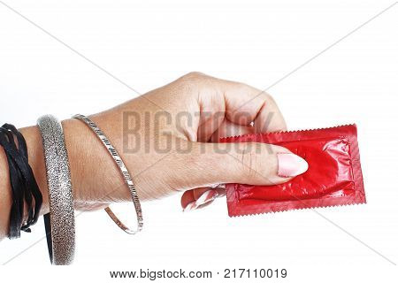 Woman hand holding condom on isolated white cutout background. Studio photo with studio lighting easy to use for every concept. STD.