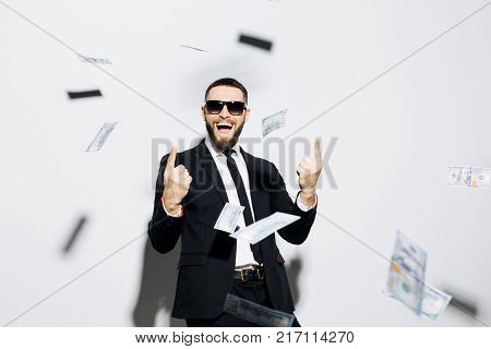 Handsome Stylish Business Man In Sunglasses And Suit Excited Scream Pointed Up On Fly Money Rain Iso