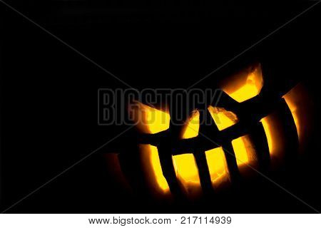 Sinisterly glowing eyes and teeth from a carved pumpkin on halloween in the lower right corner of the frame. Silhouette of the lamp of Jack on a black background.