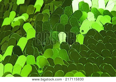 Spangle, green sequin pailette background. Mirror dress material cloth texture pattern. Tailoring stitching concept. Shiny mirrored fashion fabric. Shiny clothing material sample. Creased fabric.