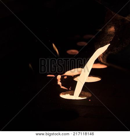 pouring molten metal into sand mold ; background