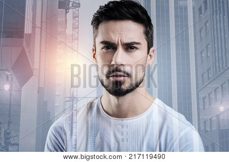 Frowning. Calm serious bearded man sitting and suspiciously frowning while watching the news and having an unpleasant feeling about it