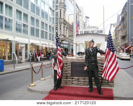 BERLIN, GERMANY - JULY 20, 2016: Checkpoint Charlie Memorial with American Soldiers. Most Well Known Berlin Wall Crossing Point Between East and West Berlin During Cold War.