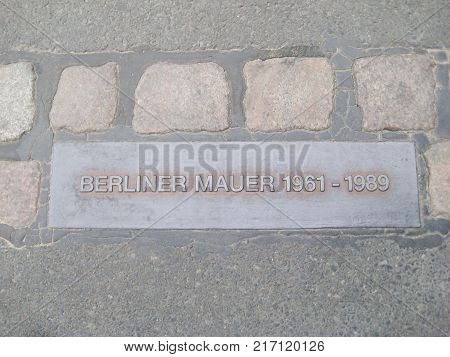 BERLIN, GERMANY - JULY 20, 2016: Berlin Wall Historical Memorial Board. Berliner Mauer Sign on the Street Pavement, Showing the Dates of the Wall Existence Between East and West Berlin, Germany.
