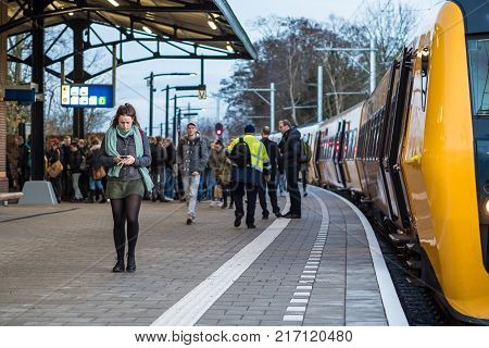KAMPEN, NETHERLANDS - NOVEMBER 30 2017: A diesel train from Zwolle arrives in Kampen and the passengers unboard. From December 10 on the diesel trains will be replaced by electric trains.