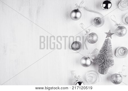 Christmas silvery glitter decorations - balls curl tapes flower on white wood board.