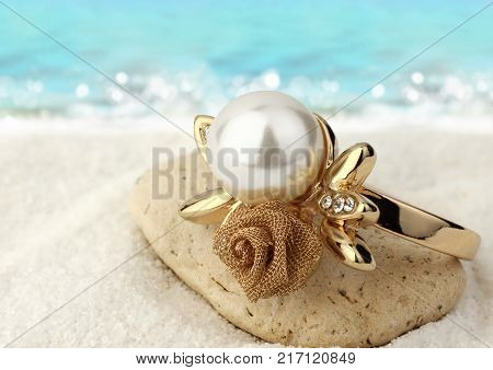 Jewelery ring with pearl on sand beach