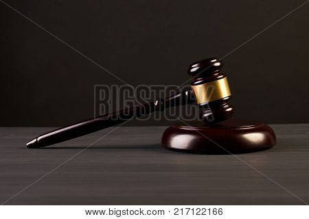 Judge's Gavel or auction mallet over black background, close-up,