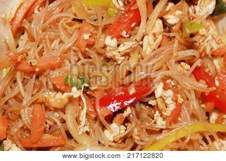 Stir-Fry Noodles Asian Traditional Wok Pasta Food Close Up Background. Rice Stir Fry Noodles Dish with Fresh Natural Vegetables: Bell Peppers, Carrot, Egg and Soy Sauce. Healthy Nutritious Meal.