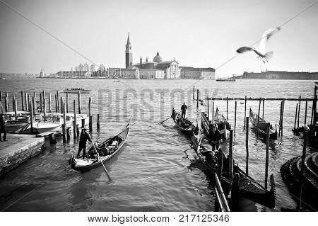 VENICE, ITALY - APRIL 11, 2017: Gondolas with tourists on background of San Giorgio Maggiore Monastery, black and white documentary snapshot. Venezia, Italy.