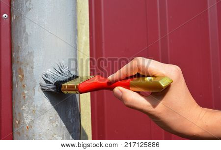 Painting metal fence with worker hand. Painting fence with red brush.