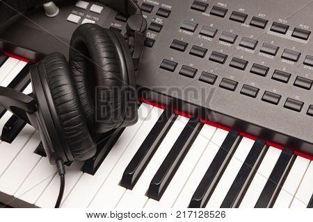 Listening Headphones Laying on Electronic Synthesizer Keyboard.