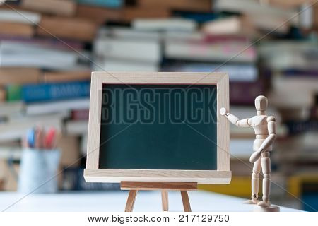 Empty green board on tripod with wood manikin pointing at it with blurred book pile and pencil cup as background. Education concept.