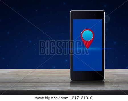 Map pin location button on modern smart phone screen on wooden table over fantasy night sky and moon Map pointer navigation concept