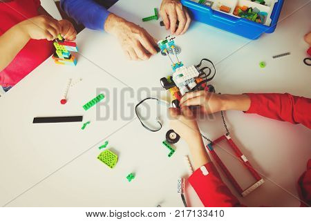 kids and teacher building robot at robotic technology school lesson, learning