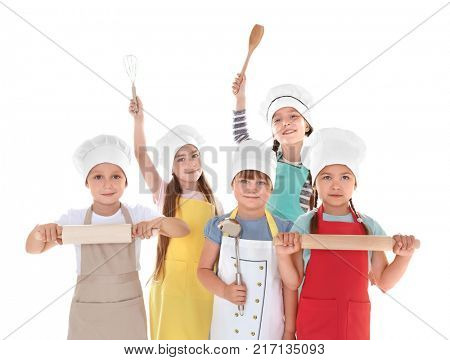 Cute children in aprons with kitchen utensils on white background