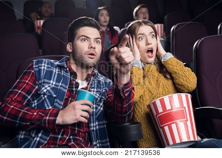 frightened couple with popcorn watching horror movie in cinema