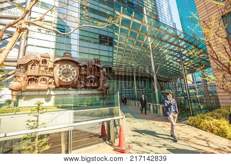 Tokyo, Japan - April 20, 2017: Japanese white-collar workers walking in Shiodome area. Business people commuter in front of Ghibli clock at Nittele Tower, Nippon Television headquarters in Shinbashi.