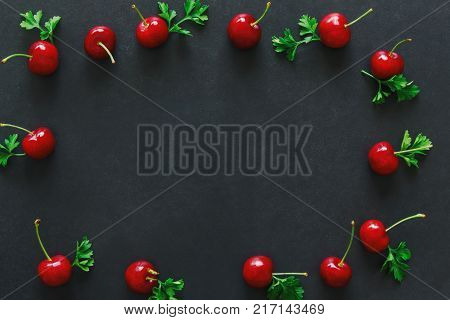 Fresh cherries on black granite table isolated background in top view flat lay. Cherry frame with copy space for web cover or banner and background. Cherry have high vitamin C and have sweet and sour taste. Red cherry is healthy and delicious fruit.