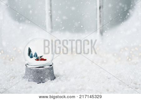 Silver snow globe with antique toy truck hauling a Christmas tree. Snowglobe is sitting outdoors on the ledge of an old wooden window in the snow.