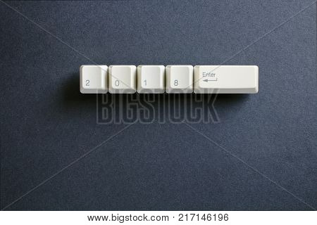 Computer keyboard keys with 2018 enter written using the white buttons on a dark background. Holiday technology concept. New year 2018 card.